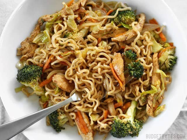 A large bowl of Chicken Yakisoba with a fork stuck in the side