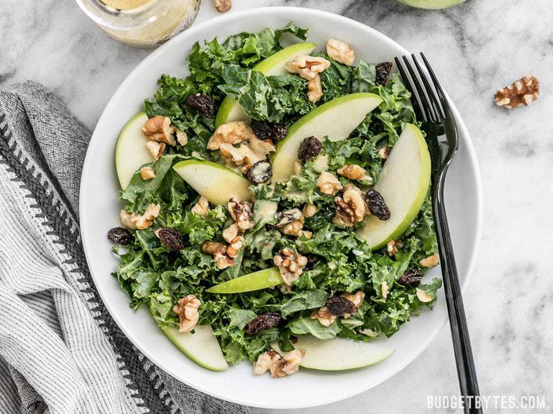 Apple Dijon Kale Salad with dressing poured over top, ready to eat