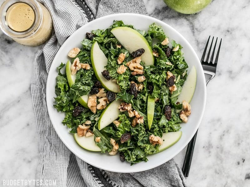 Overhead view of Apple Dijon Kale Salad in a bowl with a black fork