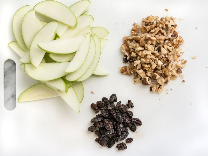 Apples Walnuts and Raisins prepped on a cutting board
