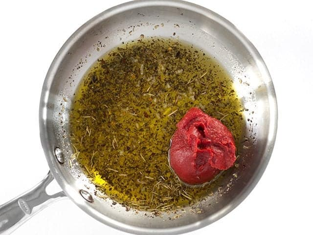 Add Tomato Paste and Honey to the skillet with oil and herbs