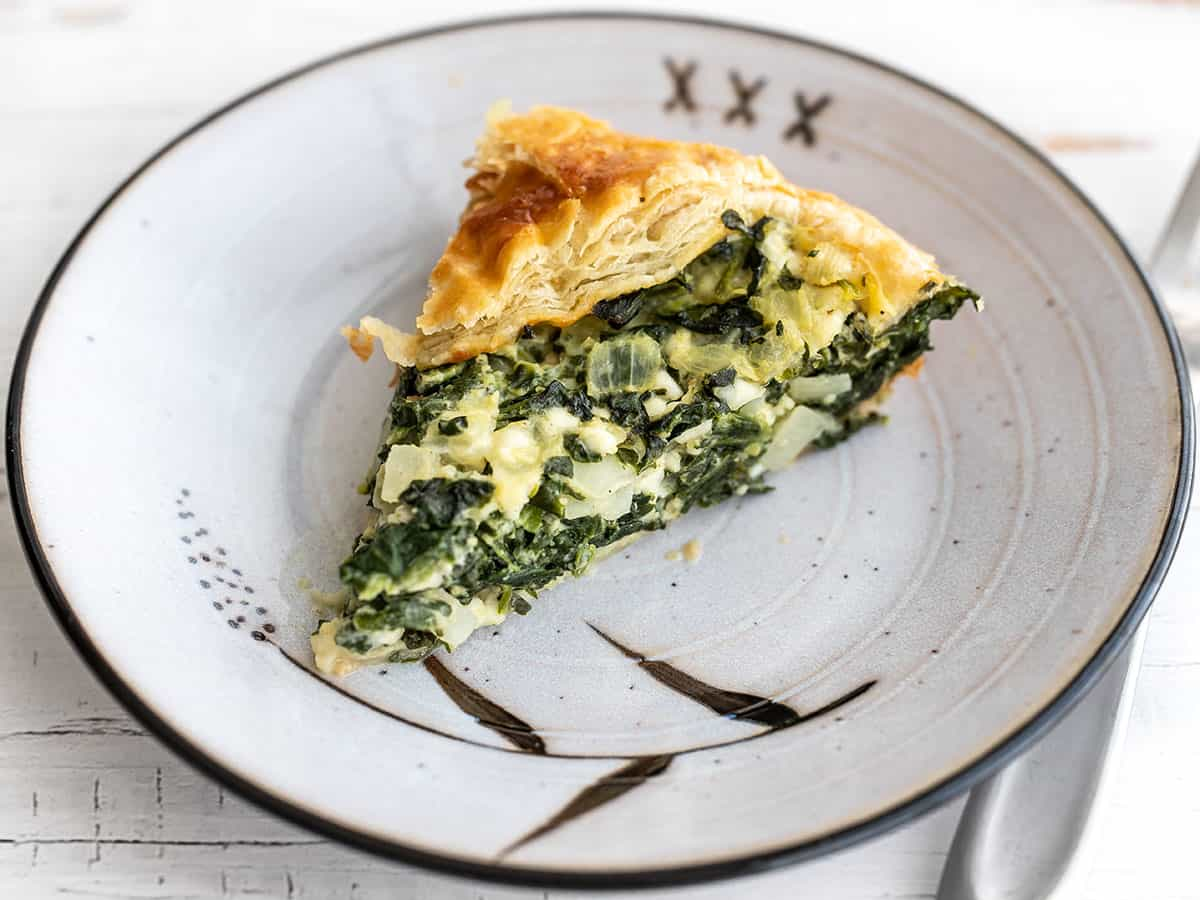 One slice of spinach pie on a plate