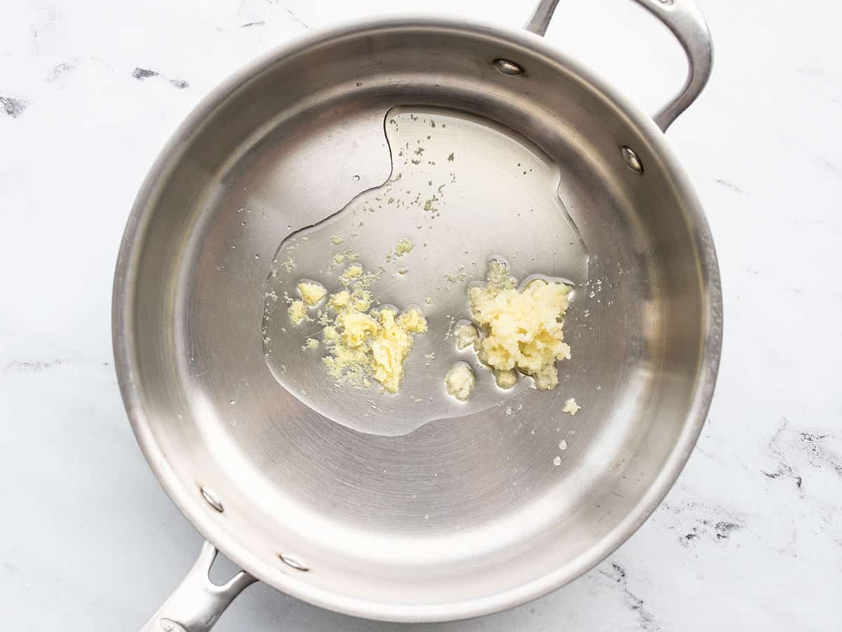 Minced garlic and grated ginger in a skillet with oil