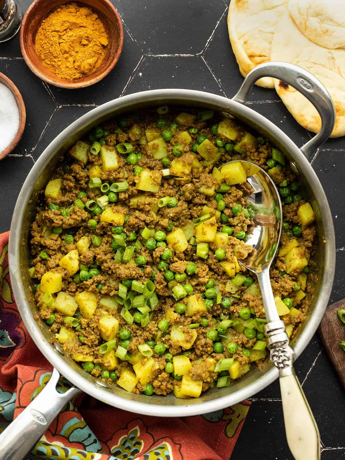 curried ground beef with peas and potatoes in a skillet with a serving spoon