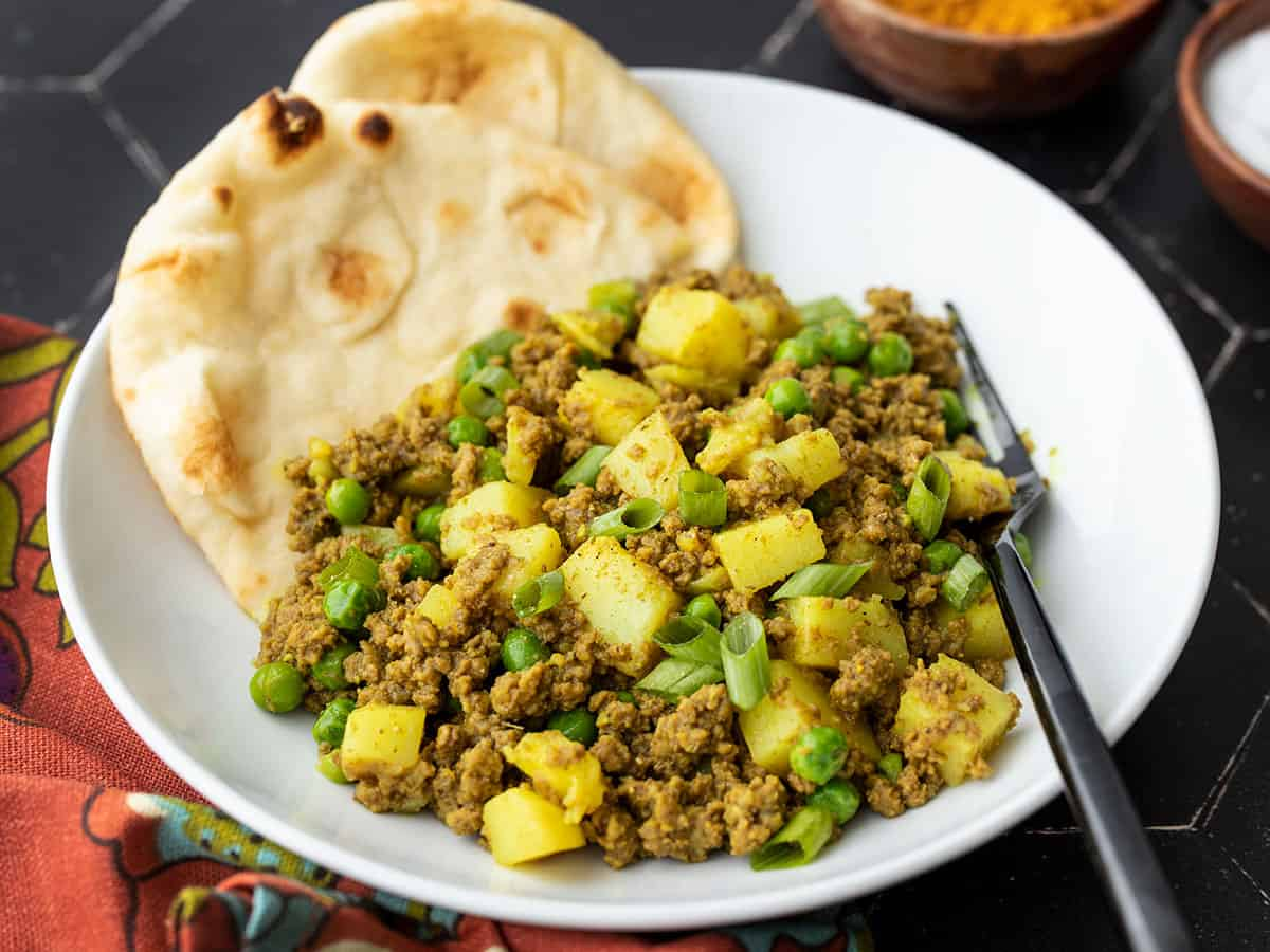 Side view of a bowl of curried beef with peas, naan in the side of the bowl
