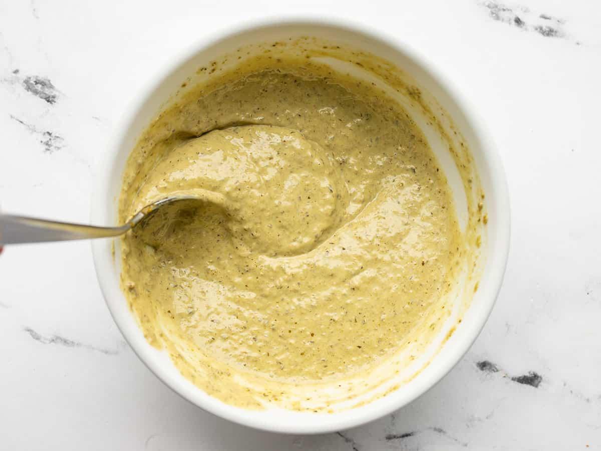 Creamy pesto dressing in a bowl being stirred