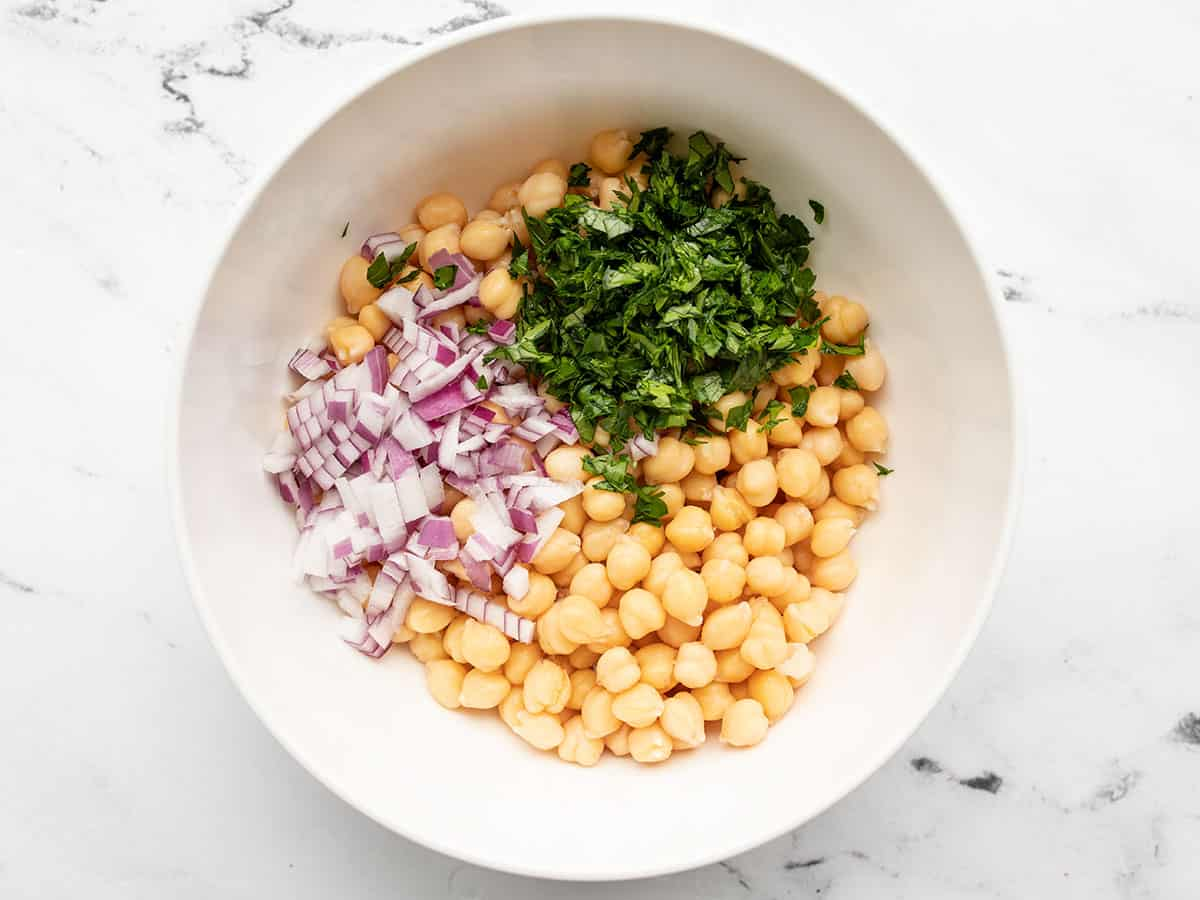 Chickpeas, parsley, and red onion in a bowl
