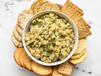 Pesto chickpea salad in a bowl surrounded by crackers
