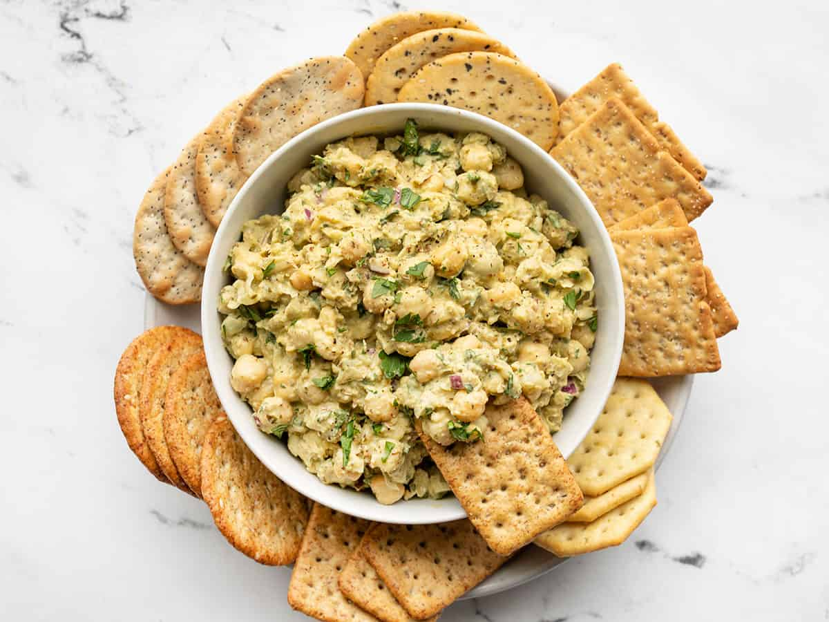 Pesto chickpea salad in a bowl with a cracker dipped into the side