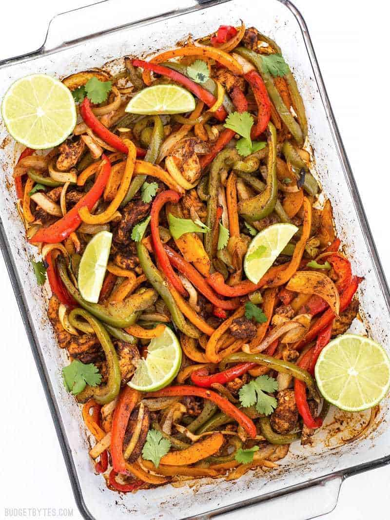 Easy Oven Fajitas in a glass baking dish with lime wedges on top