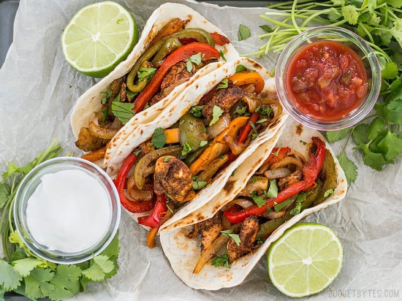 Three Easy Oven Fajitas on parchment with small dishes of salsa and sour cream