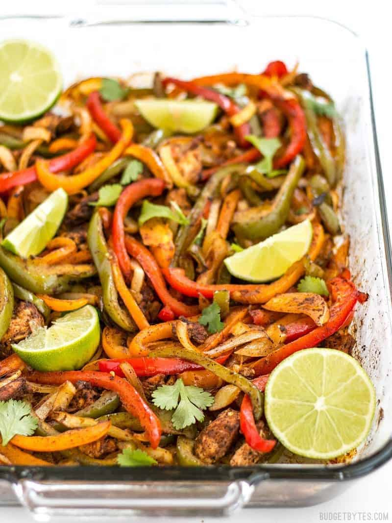 Easy Oven Fajitas in a glass casserole dish, with lime wedges on top