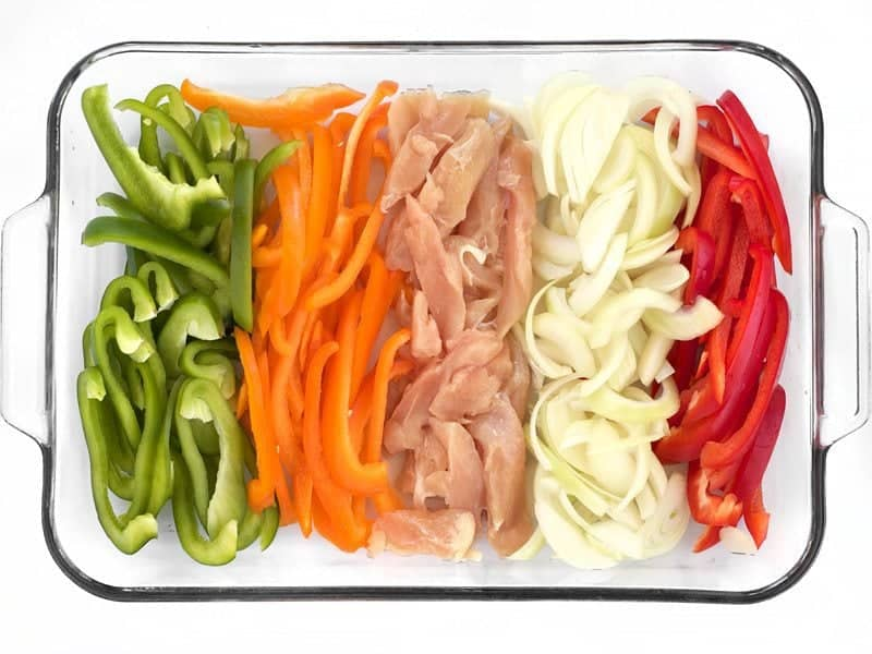 Sliced Peppers Chicken and Onion in a glass casserole dish