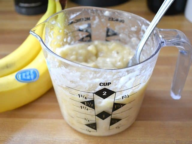 mashed bananas in measuring cup with fork