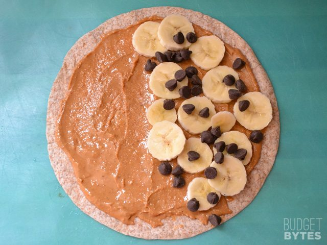 tortilla with peanut butter spread all over and chopped bananas and chocolate chips placed on one side