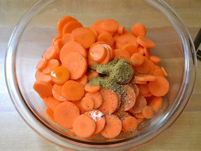 sliced carrots and seasoning in mixing bowl