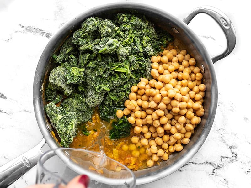 Frozen spinach, chickpeas, and water added to the skillet