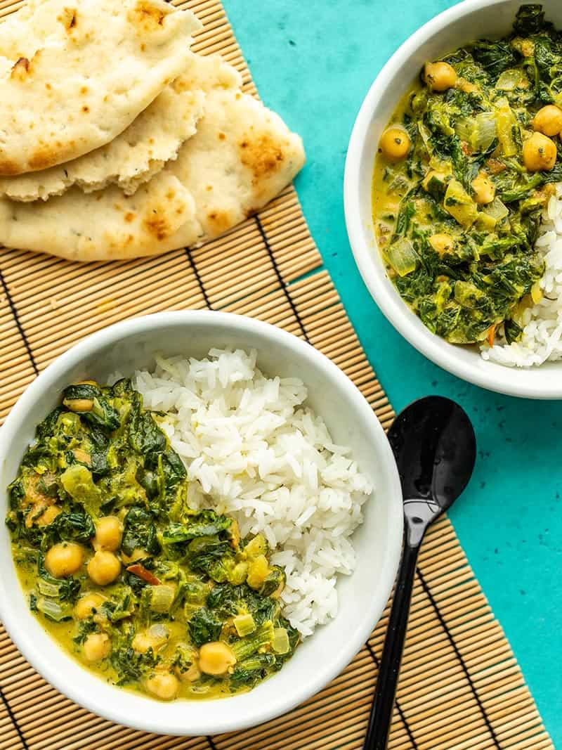 Two bowls of chana saag with rice next to a torn pieces of naan
