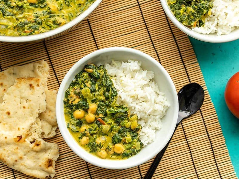 Two bowls of chana saag with rice, next to the skillet and a piece of torn naan
