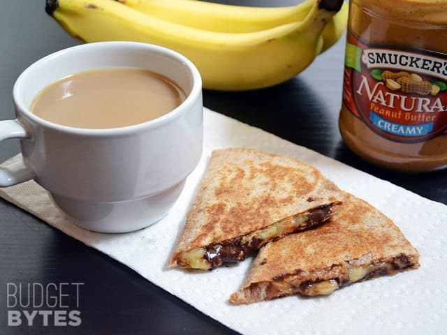 Two slices of a Peanut Butter Banana Quesadilla with a cup of coffee next to it