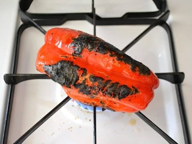 red bell pepper cooking on open flame on stove top
