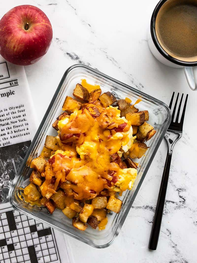 One Country Breakfast Bowl meal prep container on a table with a morning paper, mug of coffee, and an apple.