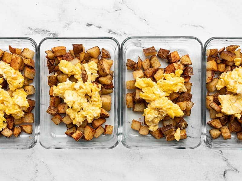 Add eggs to roasted potatoes in meal prep containers