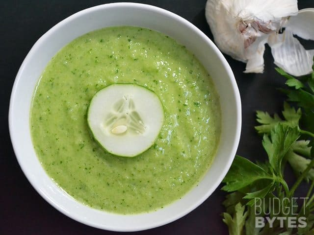 Top view of a bowl of Green Gazpacho with a sliced cucumber on top