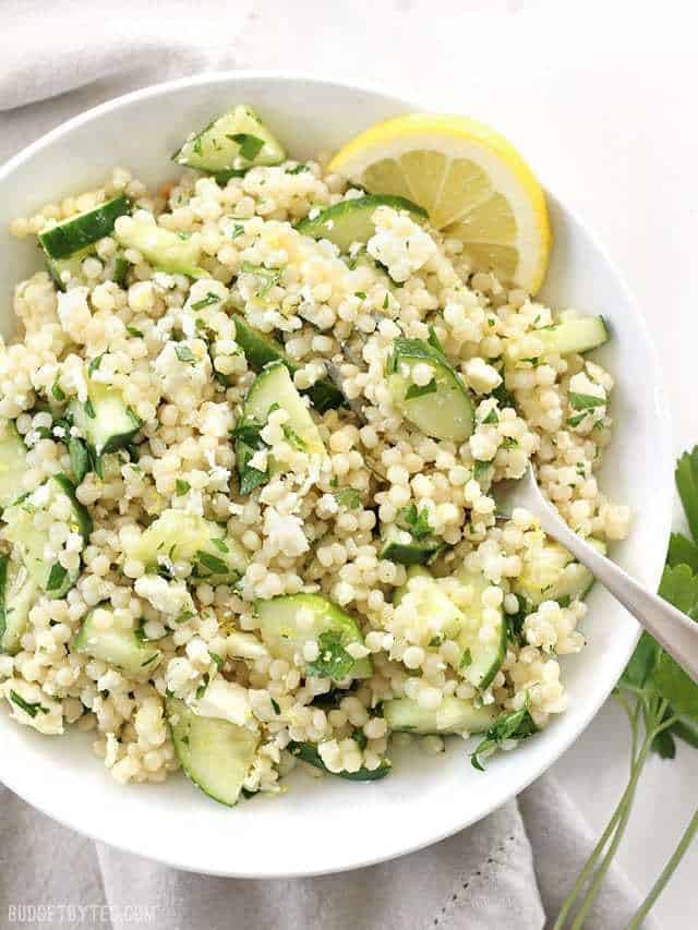 Close overhead view of a large bowl of lemony cucumber couscous salad, with a lemon wedge stuck in the side.