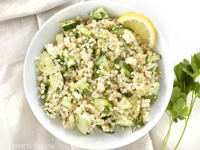 Overhead view of a white bowl full of Lemony Cucumber Couscous Salad, fresh parsley on the side