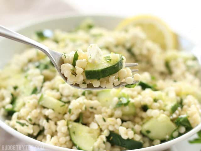 Close up of a forkful of Lemony Cucumber Couscous Salad, with the bowl in the background.