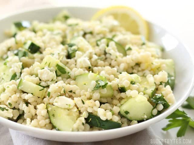 Side view of a bowl of Lemony Cucumber Couscous Salad, garnished with fresh parsley and lemon wedges.