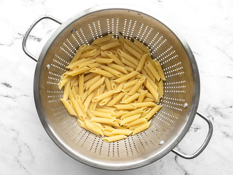 Cooked pasta in a metal colander