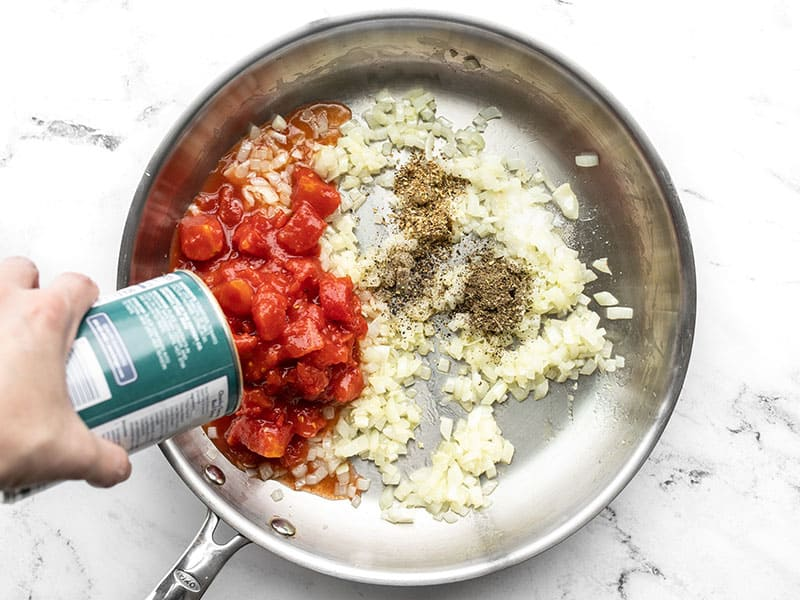 Diced tomatoes being poured into the skillet, with basil, oregano, and pepper.