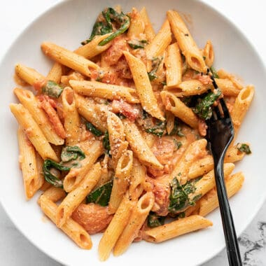 Overhead view of a bowl full of creamy tomato and spinach pasta, a black fork in the side