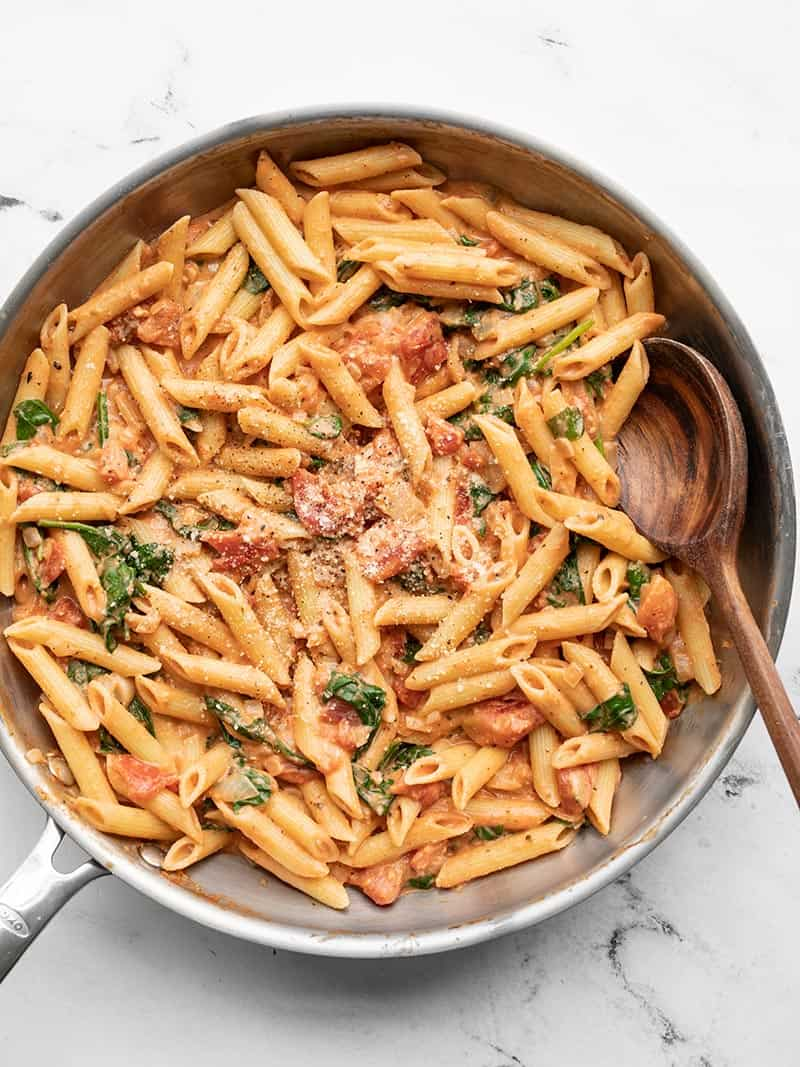Overhead view of the creamy tomato and spinach pasta in the skillet with a wooden spoon.
