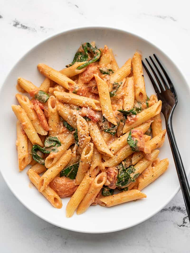 Overhead view of a bowl of creamy tomato and spinach pasta, with a black fork in the side