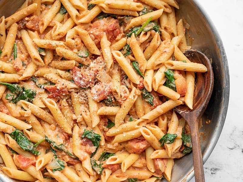 Close up overhead view of creamy tomato spinach pasta in a skillet, a wooden spoon in the side