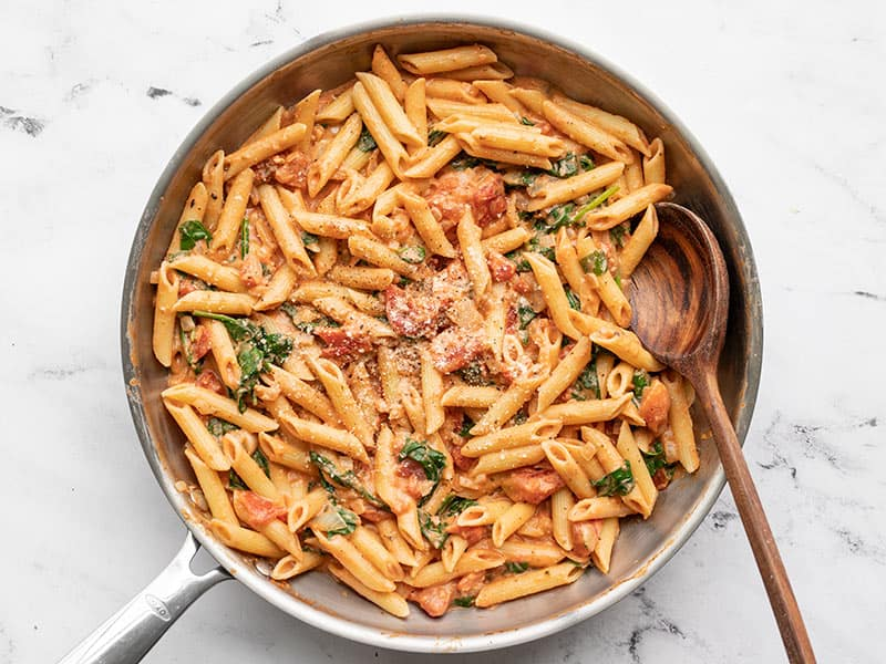Finished creamy tomato and spinach pasta in the skillet with a wooden spoon