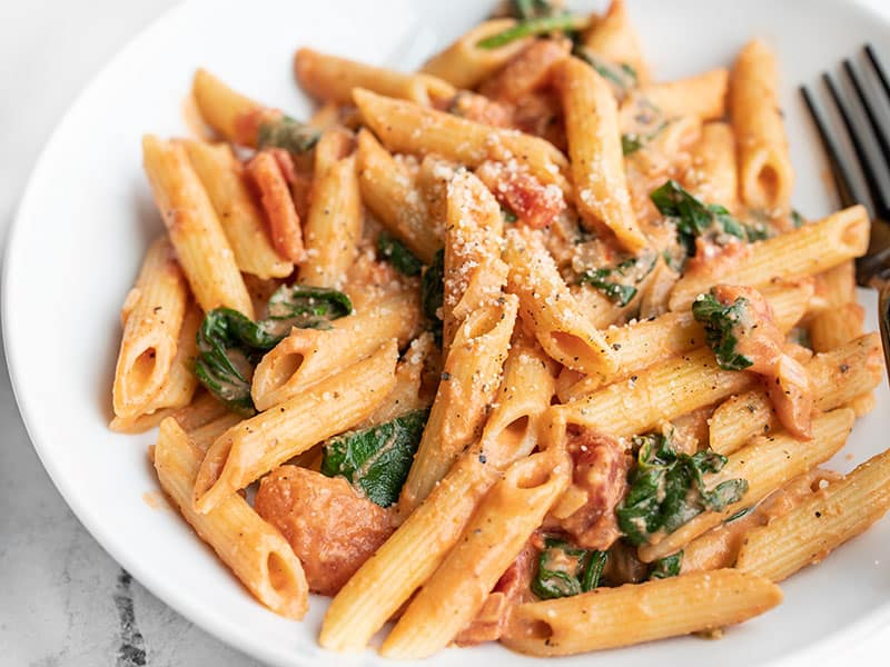 Close up side view of a bowl of creamy tomato and spinach pasta