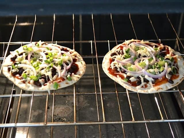 two pizzas baking on wire rack in oven