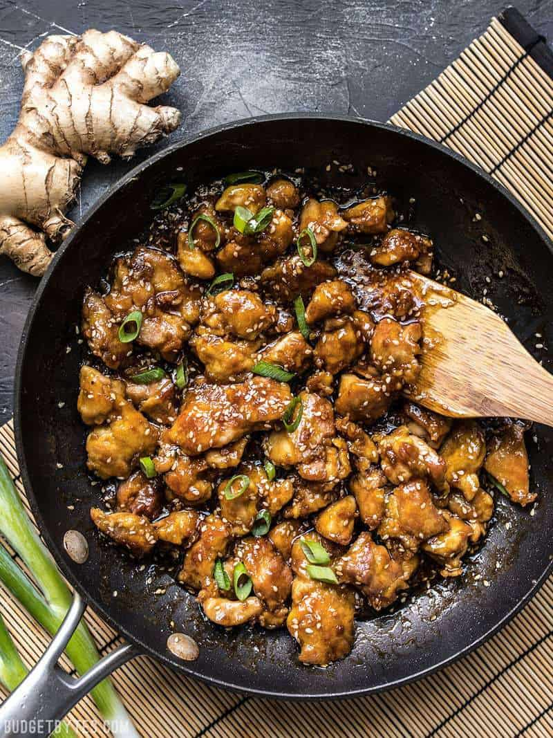 A skillet full of easy sesame chicken with a wooden spatula on a bamboo mat.