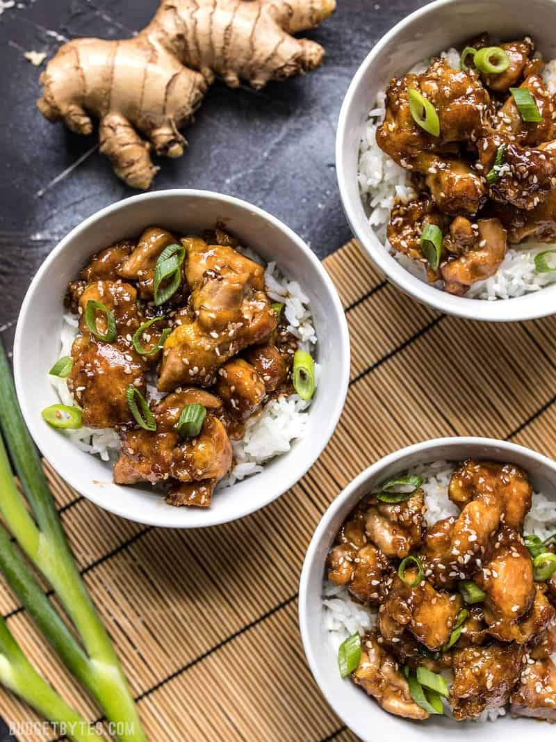 Three bowls of easy sesame chicken on a bamboo mat with ginger and green onion next to the bowls.