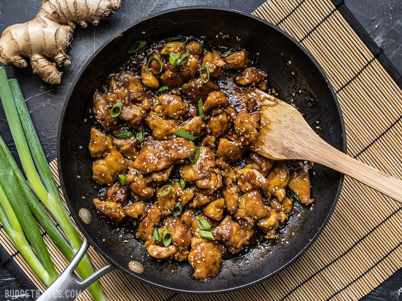 Finished easy sesame chicken in a skillet with a wooden spatula on a bamboo mat with green onion and ginger near by.