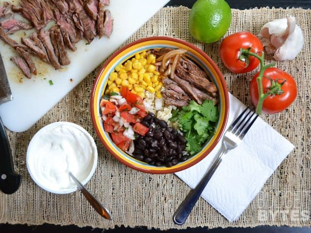 Top view of building a Southwest Steak Bowl with ingredients