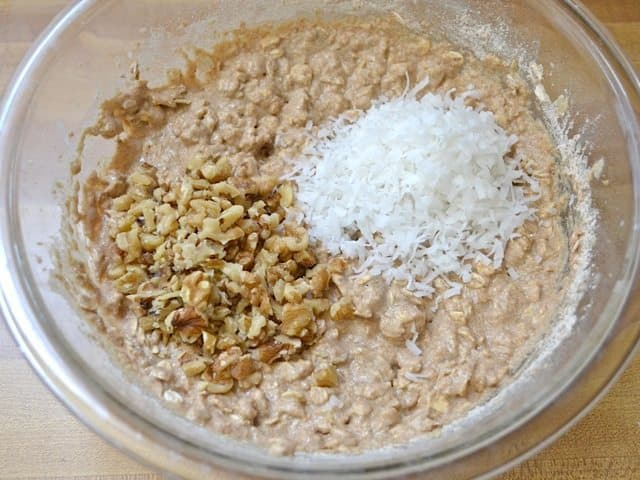 Chopped walnuts and shredded coconut added to mixing bowl
