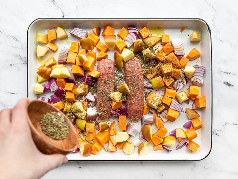 Diced apples, sweet potatoes, and sausage being seasoned with herbs
