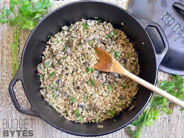 Top view of Baked Barley with Mushrooms in pot with wooden spoon