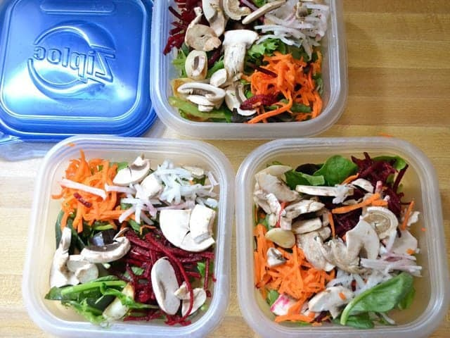 Salad divided into three different Tupperware containers