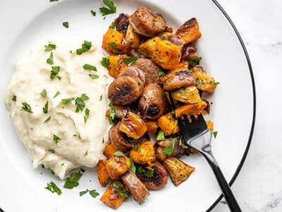 Oven roasted autumn medley on a plate with mashed potatoes and a black fork